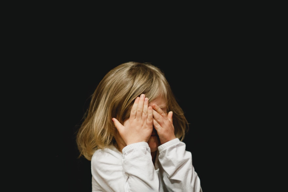 girl with hands covering face due to pinkeye