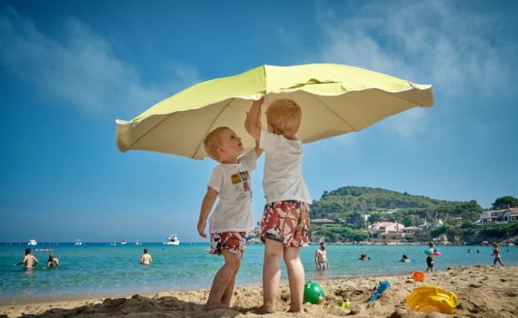 kids under beach umbrella to prevent sunburn