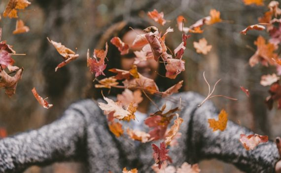 woman with fallen leaves - fall health concerns