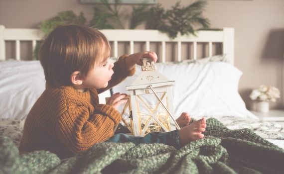 celebrate at home - young boy on bed with holiday lantern