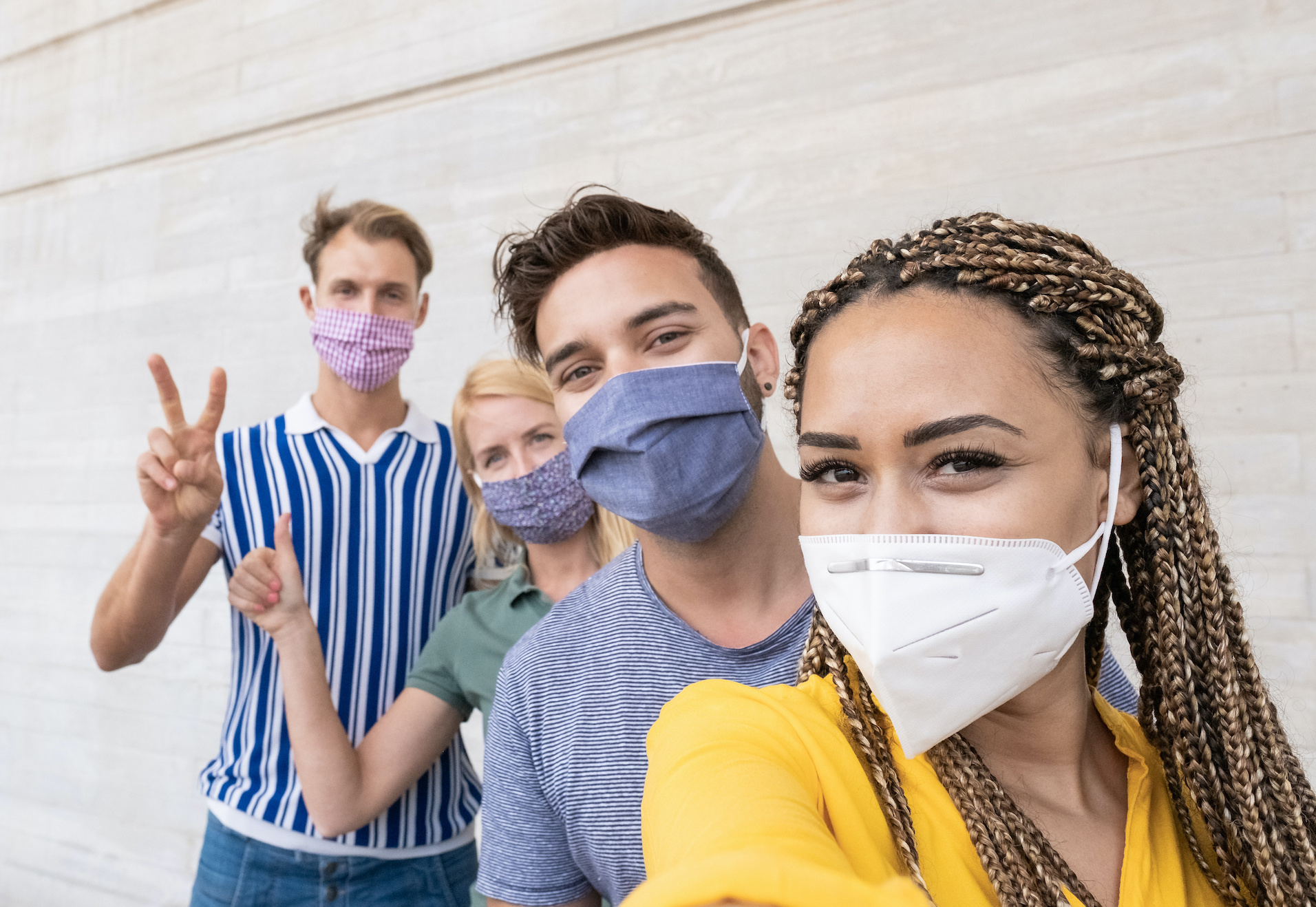 young friends in a selfie wearing masks, safely attending an event with on-site covid-19 testing