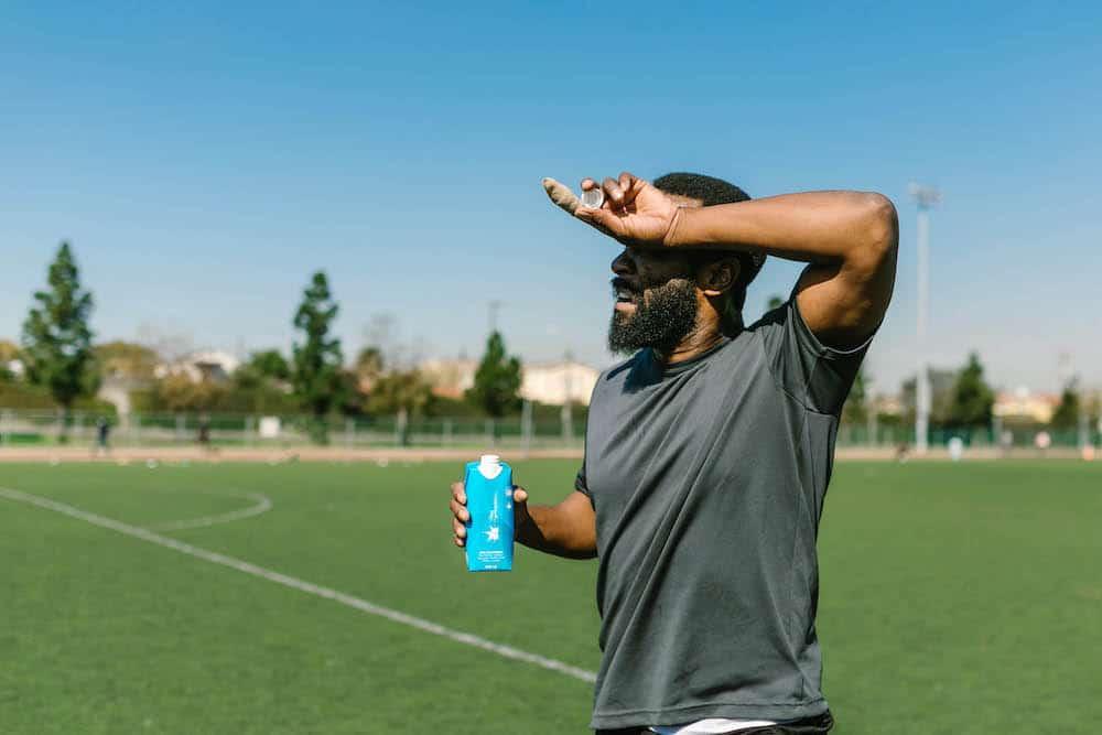 heat-related illness - man on sunny soccer field, shielding eyes from sun, drinking water